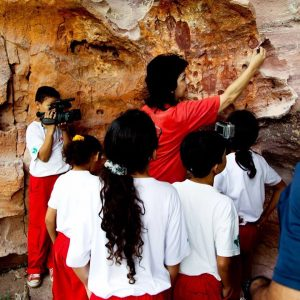 Crianças e educadora analisam marcas em pedra. Foto: divulgação.