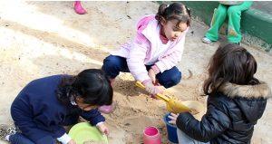 3 crianças brincam em tanque de areia.