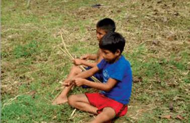 Educação escolar indígena - inovação, participação docente e avaliação. Duas crianças brincam sentadas no chão. Crédito: reprodução