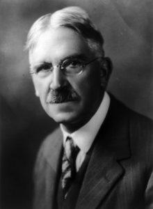 John Dewey, filósofo americano, usa óculos e veste terno e gravata. Imagem em preto e branco