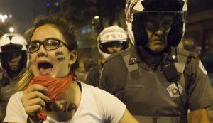 Imagem de capa do Livro Escola Pública. Tempos difíceis, mas não impossíveis mostra uma estudante se manifestando e um policial ao seu lado