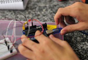 Imagem mostra duas mãos mexendo em aparelho eletrônica em referência ao mundo maker