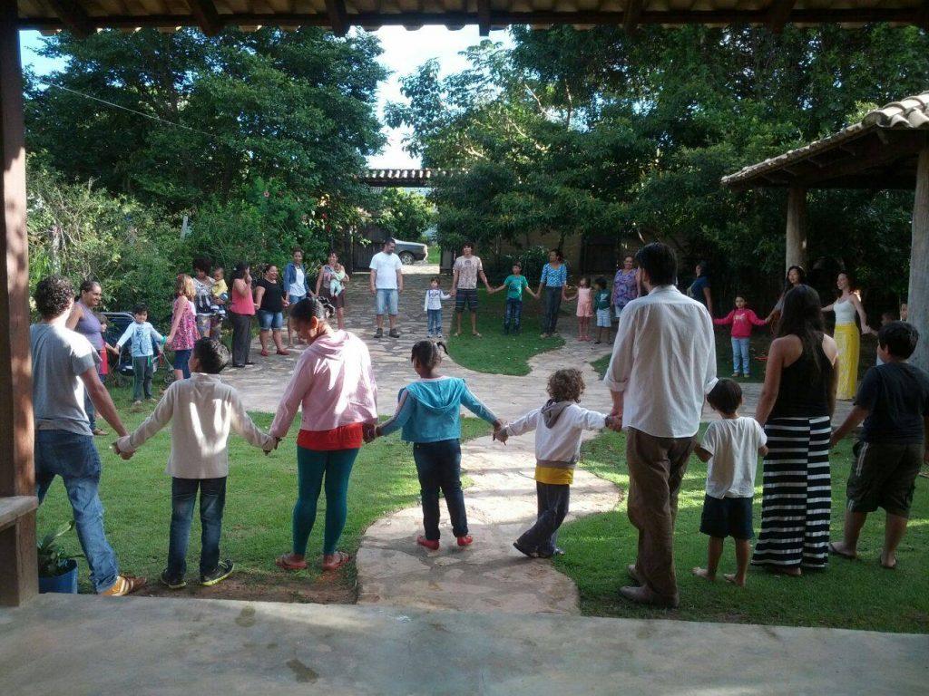 Imagem da reportagem mostra pais e crianças de mão dadas em roda. Crédito: Centro de referências em educação integral