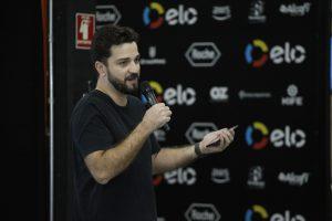 Hygor Amorim, diretor de Sementes da Educação, usa camiseta preta e fala ao microfone